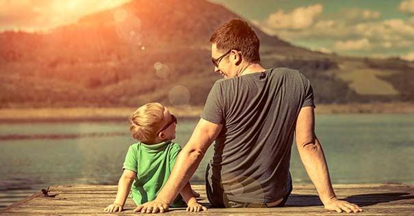 padre-e-hijo-sentados-muelle-rio-riendo-060716