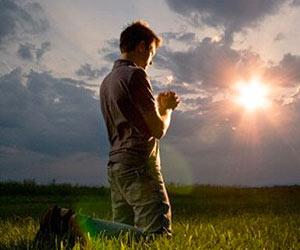 joven-orando-campo-amanecer
